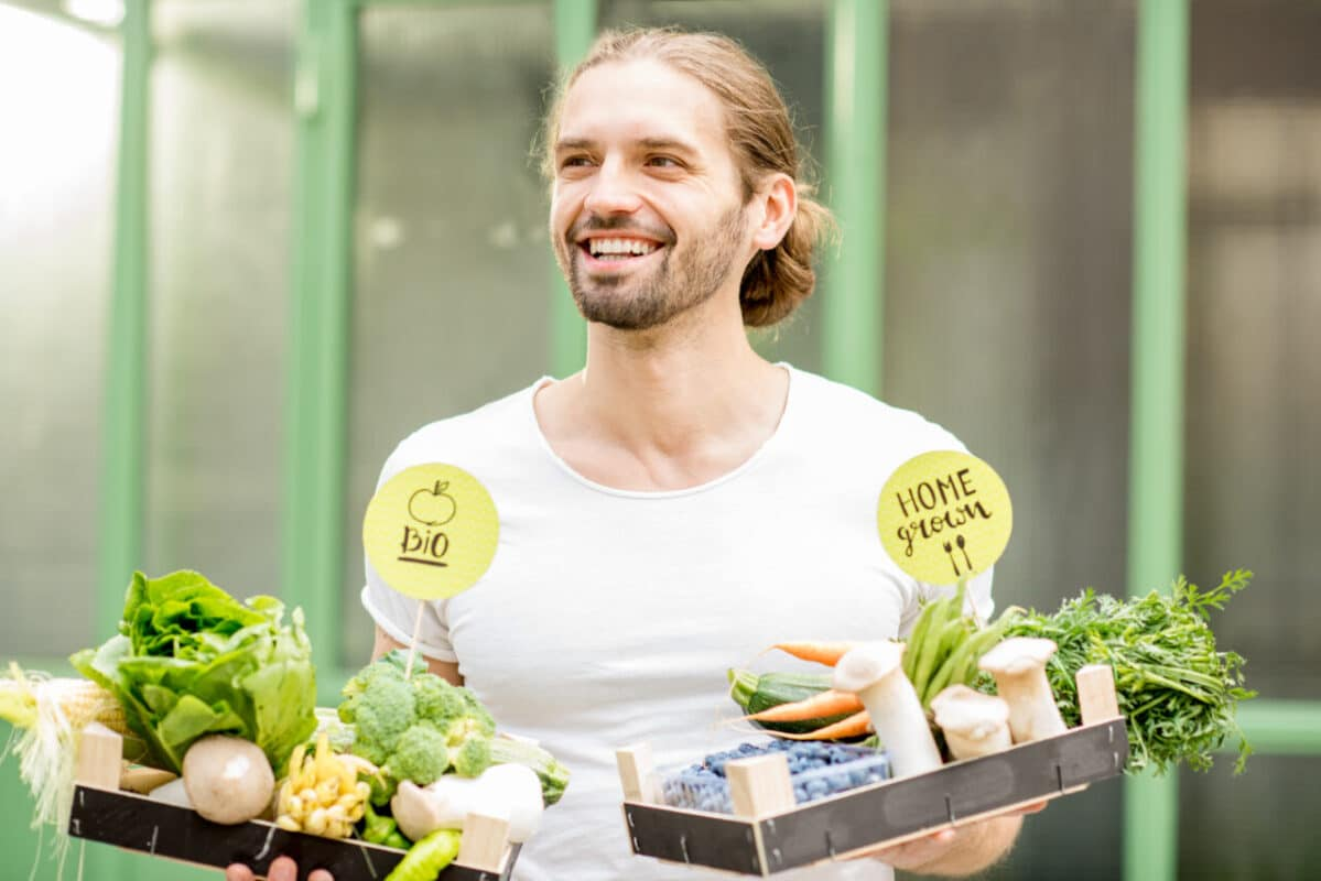 Athlete with box full of fresh raw vegetables